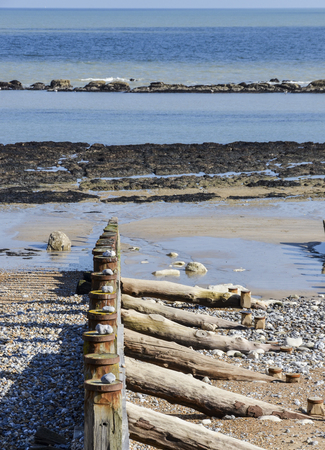 A row of groynes on the beach with a stone placed on the top of each one Standard-Bild - 121438263