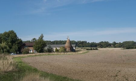 A round oast house on a farm in the countryside in Kent, UK Фото со стока