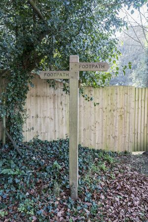 A wooden footpath directional sign in the countryside