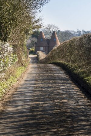 A country lane leading to an oasthouse in the Kent countryside in Spring