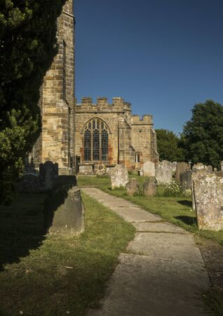 Path through graveyard at St Laurence Church in the ancient village of Hawkhurst, Kent, UK