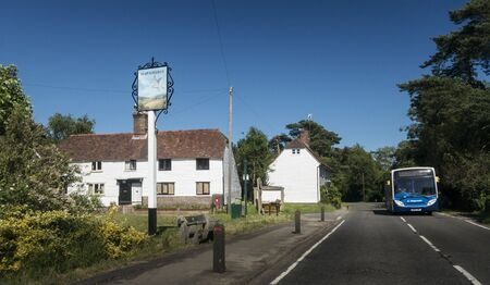 The ancient village of Hawkhurst in Kent, UK, with an oncoming bus on the road Фото со стока