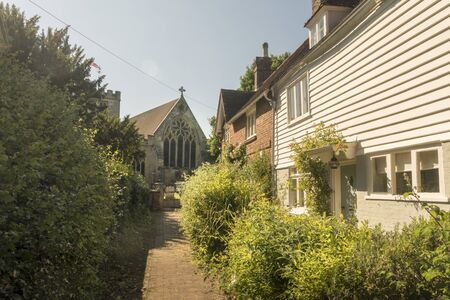 Ancient cottages and passage leading to St Laurence church in the village of Hawkhurst, Kent, UK Фото со стока