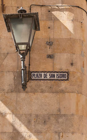 Street lamp and name sign on a stone wall  in the city of Salamanca, Spain