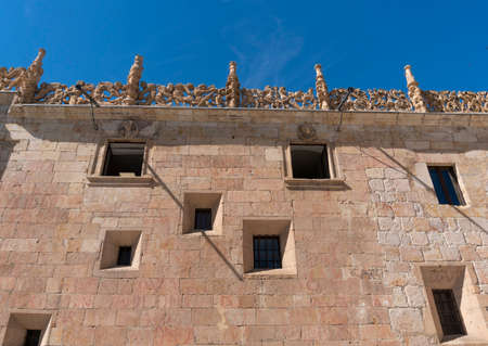 Windows in an ancient stone wall  in the city of Salamanca, Spain