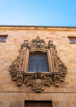 A barred ornate window on a stone wall  in the city of Salamanca, Spain