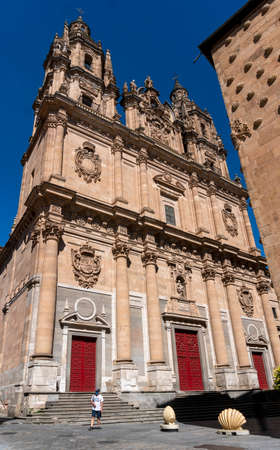 A man wearng a face mask to protect from Corona Virus, in front of a Baroque Catholic church  in the city of Salamanca, Spain 新闻类图片