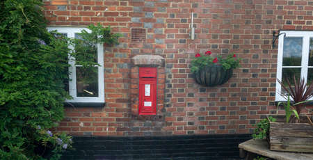 A red Victorian post box in the wall of The Bell public house in the village of Smarden, Kent, UK Editorial