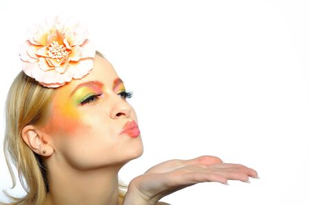 Concept of summer fashion woman with creative eye make-up in yellow and green tones sending kisses. copy-space photo