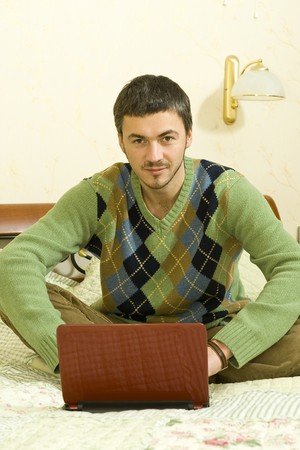 Picture of young handsome man working online from his house on the laptop Stock Photo - 6959560