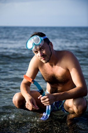 Young happy handsome summer diving man with swimming mask and snorkel preparing to dive in blue sea Stock Photo - 6959564
