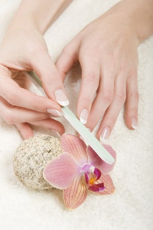 Beautiful hands with perfect french manicure and nail file photo