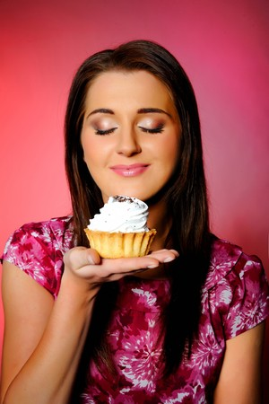 young beautiful girl eating small sweet cake. red background. copy-space. focus on the cake Stock Photo - 6959602