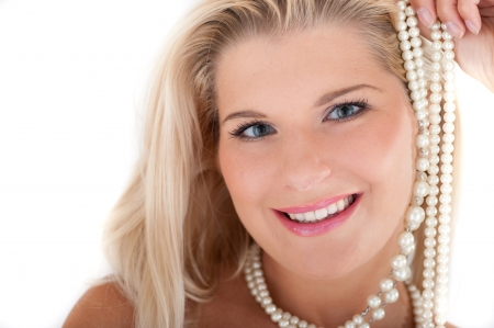 Young beautiful woman with healthy skin and white teeth holding pearl necklace photo