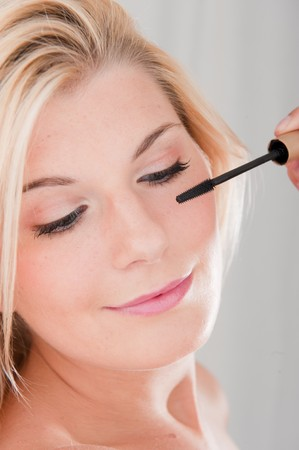 Young beautiful woman with pure healthy skin applying mascara make-up on her lashes photo