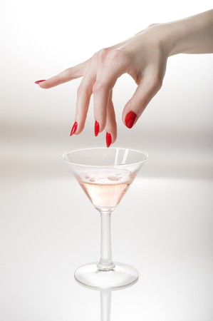 Beautiful hand with perfect red manicure holding martini glass .  photo