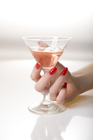 Beautiful hand with perfect red manicure holding martini glass .