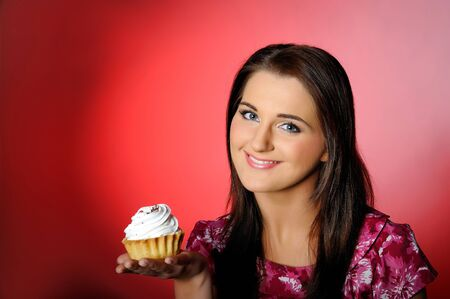 young beautiful girl eating small sweet cake. red background. copy-space Stock Photo - 7016923