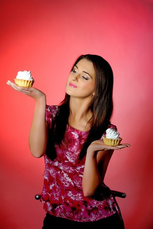 young beautiful girl eating two small sweet cake. red background. copy-space Stock Photo - 7016907