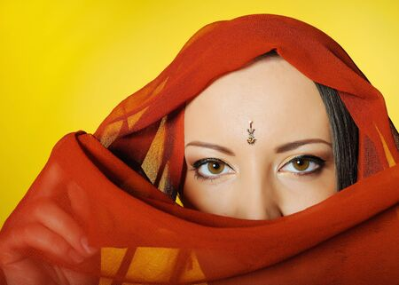 Young beautiful woman eyes in indian traditional jewellary, bindi , sari dress and makeup. yellow background Stock Photo