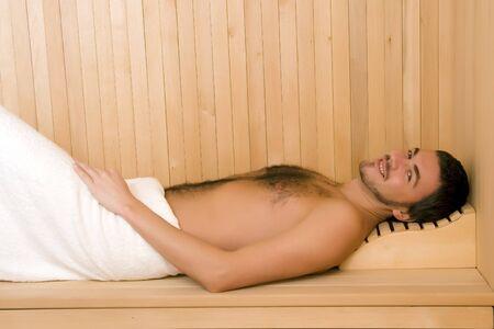 cabine de douche: Jeune homme beau dans une serviette relaxante dans un sauna en bois russe
