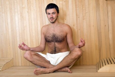 Young handsome man in a towel relaxing in a russian wooden sauna Stock Photo - 7016903