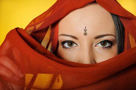 Young beautiful woman eyes in indian traditional jewellary, bindi , sari dress and makeup. yellow background photo