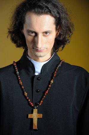 toog: conceptuele portret van Praying priester met houten kruis bidden. gele achtergrond