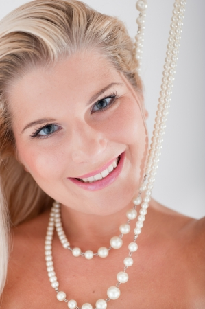 Young attractive woman with white teeth and pearls smiling photo