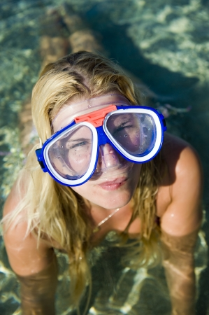 scuba goggles: Young happy beautiful summer diving woman with swimming mask and snorkel preparing to dive in blue sea