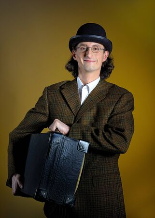 Portrait of funny retro man with suitcase. yellow background photo
