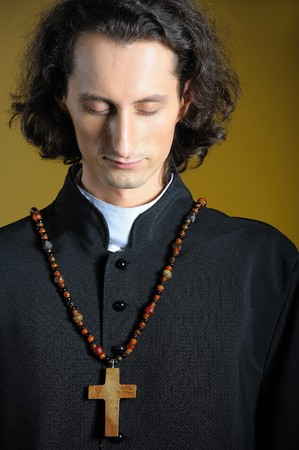 priesthood: conceptual portrait of Praying priest with wooden cross praying. yellow background Stock Photo