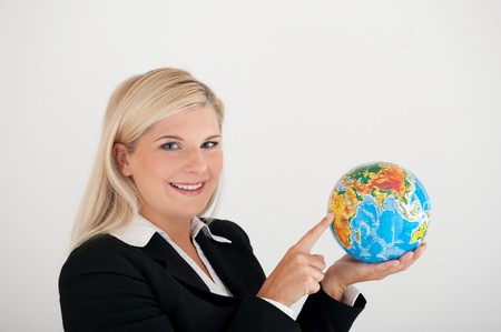 online internet presence: young business woman in a black suit with a world globe
