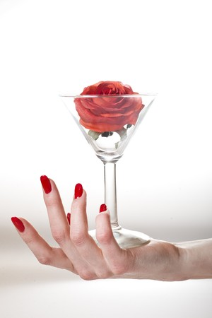 Beautiful hand with perfect red manicure holding martini glass with red rose inside. youth and beauty concept Stock Photo