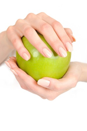 Green apple in a beautiful hand of woman with perfect nail manicure. white background