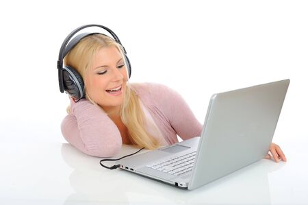 Pretty young girl listening to the music with headphones from her laptop. isolated on white background Stock Photo - 7281117