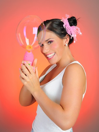 Beautiful happy woman blowing soap bubbles and having fun. pink background Stock Photo - 7415539
