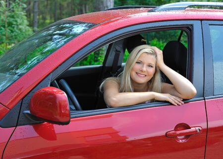 beautiful woman driver in red shiny car outdoors smiling photo
