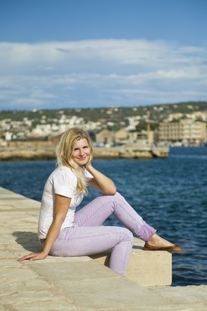 Young beautiful fresh woman smiling and relaxing near the blue sea in Grece photo