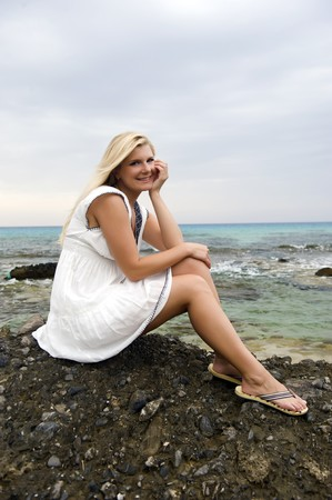 Young beautiful fresh woman sitting on a stone near the blue stormy sea photo
