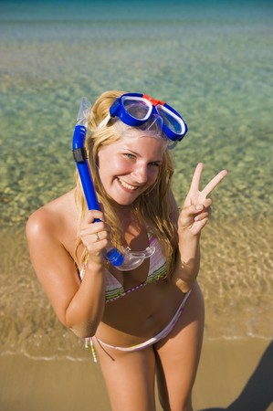 Young happy beautiful summer woman with swimming mask and snorkel preparing to dive in blue sea Stock Photo - 7417735
