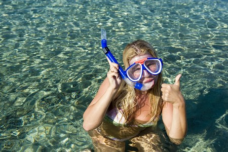 Young happy beautiful summer diving woman with swimming mask and snorkel preparing to dive in blue sea photo