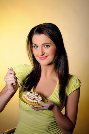 young beautiful girl eating small sweet cake. yellow background Stock Photo - 7417766