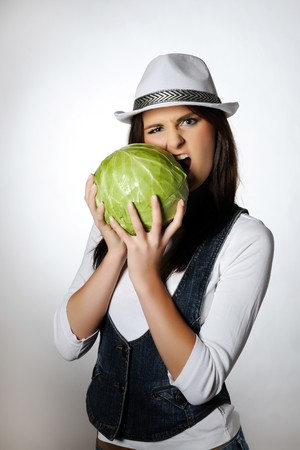 Young pretty woman eating green cabbage  photo