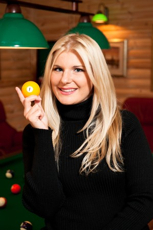 Beautiful young woman with billiard ball in club photo