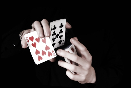 trick: Young magicians hands holding a lot of play cards. black background