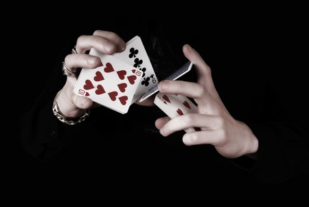 Young magicians hands holding a lot of play cards. black background photo