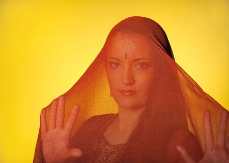 burka: Young beautiful muslim woman coverer in hijab. yellow background