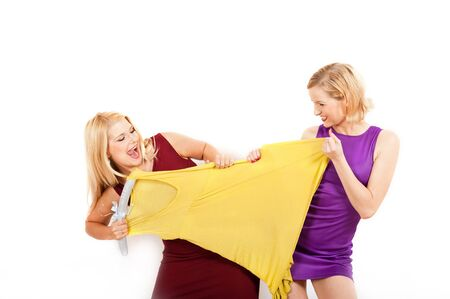 two beautiful shopping girls fighting for a dress. isolated