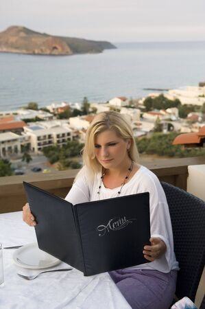 Young beautiful woman on vacation is looking in menu in small restaurant with a view on the sea photo